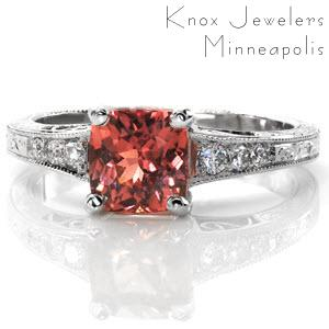 The 1.00 carat cushion cut Padparadscha Sapphire in this design is mesmerizing with its rare, luscious color. The tapered band has tantalizing details to compliment the center stone; the filigree and side stones near the top and the splendid hand engraving below.
