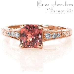 Rose gold custom engagement ring in Columbus with a hand engraved and filigree band with a cushion cut orange pink sapphire at its center.
