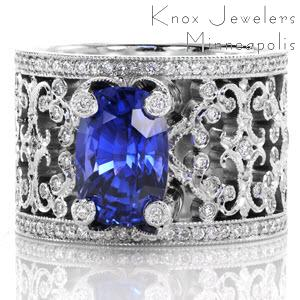 Intricate pierced scrolls created in 14k white gold and adorned with bead set diamonds. For Design 2352, the natural 3.50 carat cushion cut blue sapphire is embraced with four regal, diamond capped prongs. Hand applied milgrain finishes our Knox Signature heirloom band.