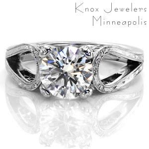 This design is as unique as it is breathtaking. The 1.70 carat round brilliant center diamond is nestled between a split shank band that loops instead of merging with the center setting. The top of the band is enthralling with hand engraving and a few surprise diamonds and the sides have filigree.