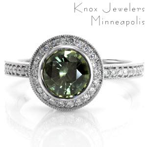 The forest green hue of the 1.50 carat gemstone gives the Ashley design a nature-like quality. Bead set diamonds encircle the round sapphire to enhance the deep green of the center gem. Similar micro pavé diamonds line the band for a completed look.