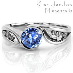 Design 2385 is a sophisticated solitaire featuring a natural 0.75 carat round cut blue sapphire. The high polish band portrays flowing movement as it embraces the center stone with a half bezel. The open pockets between the split shank make the perfect frame for filigree curls, keeping the design delicate.
