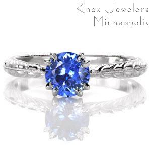 The rich, vibrant blue against the bright, white luster of the metal is a breathtaking sight. A 1.0 carat round blue sapphire is securely held by claw prongs and is detailed at the bottom with two surprise diamonds. The milgrain knife-edge is accented with wheat pattern engraving on each side.
