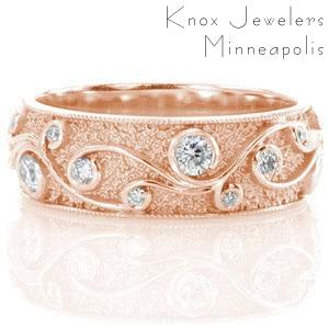 Rose gold wedding ring with filigree curls, stippled background and round cut diamonds.