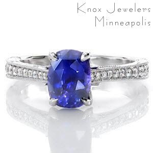 The magnetic color of this 1.50 carat cushion cut sapphire is a perfect focal point on this graceful, vintage-inspired ring. The top of the band is adorned with bead set diamonds while the sides are handsomely appointed with hand engraving, filigree, and three petals with diamonds delicately placed.