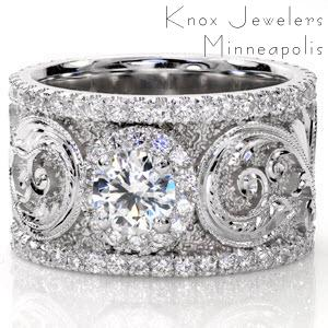 Calabria is a stunning work of art. A 0.50 carat center stone is accented with a micro pavé halo. The scroll work along the wide band is magnificent with hand engraved detail and faceted stipple background that captures the light. Two rows of micro pavé diamonds frame the picturesque design.
