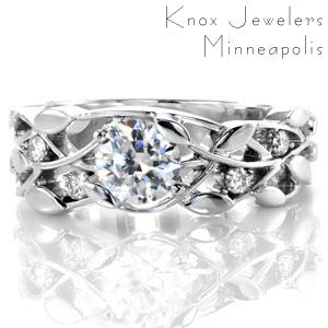 Rochester custom engagement ring with a round diamond center and a nature inspired leaf and vine patterned band.