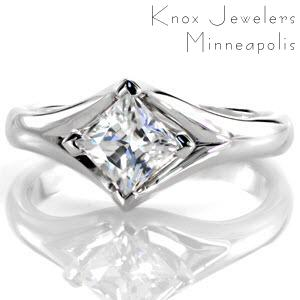 The fluid split shank design flawlessly joins to secure a 1.00 carat kite set princess cut diamond. With four sophisticated chevron prongs capturing the diamond, the band splits and gracefully frames the center stone. Moselle is truly a unique setting that is beautiful at every angle.