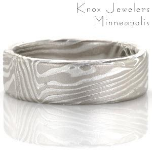 This striking wedding band is created from a sterling silver and 14k palladium Mokume Gane. The seamless pattern resembles wood grain and is created by hand in our Minneapolis Production studio. Once the design is complete the ring in put into a silver etching solution which creates dimension on the piece.