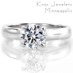 This classic solitaire design features a sleek wide band and a 1.00 carat round brilliant center diamond. The side profile reveals a beautiful row of micro pavé surprise diamonds at the base of each side of the center stone. The prongs extend and curve down to meet the bridge of the band.
