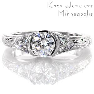 This charming design features a 0.60 carat round brilliant cut center diamond in a half bezel setting. The band tapers slightly and elegant hand engraving adorns the top of it up to a cluster of micro pavé on each side of the center stone. The edges of the band have a milgrain texture.