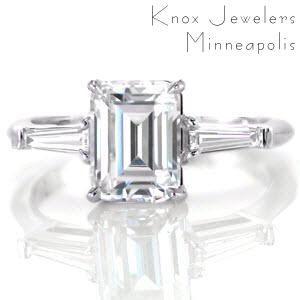 Columbus classic custom engagement ring on a slim polished band with an emerald cut diamond center bordered on either side by a tapering banquette diamond.