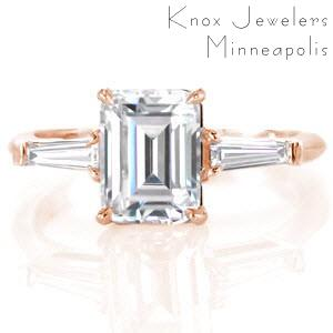 Dayton classic custom engagement ring on a slim polished band with an emerald cut diamond center bordered on either side by a tapering banquette diamond.
