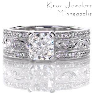 This stunning design features a very wide band with a 1.00 carat radiant cut center diamond. There is a row of micro pavé accenting each edge of the band with a row of hand engraved patterns in the middle. The engraving is a raised, relief style with the design being higher than the background.