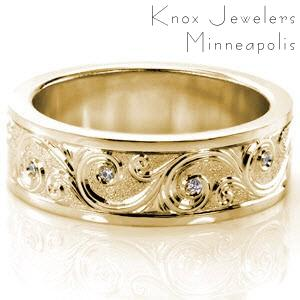 Grand Rapids custom wide band ring with high polished rails bordering a central scroll style hand engraving pattern with bezel set diamonds and a sandblasted background.