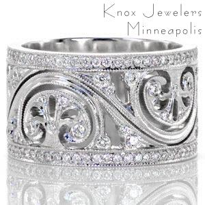 This vintage inspired wide band features a flowing pattern with pierced elements and art deco inspired fan shapes. There are bezel set diamonds within the center design and two rows of micro pavé diamonds framing the pattern. The edges of each section are detailed with milgrain texture for added definition.