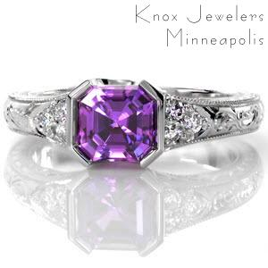 The striking 1.30 carat asscher cut natural purple sapphire is set perfectly within Design 2492. The half bezel design is complimented by round diamond side stones. The hand engraved band displays fine milgrain edges. Four pockets within the 14k white gold band frame intricate hand wrought filigree scrolls.