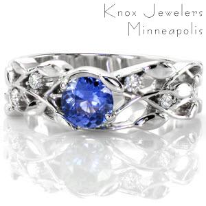 The Sapphire Allamanda creates a labyrinth of trailing vines and petals. In 14k white gold, the open pockets nest a natural 0.50 carat round cut sapphire of deep blue. Rare petal prongs join the center stone into the design and round cut diamonds add the right touch of sparkle to the band.