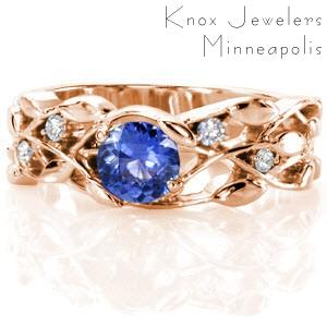 Rose gold engagement ring in New Orleans with nature inspired patterns and blue sapphire center stone.