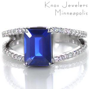 Clean lines and royal hues make Design 2506 an imperial piece. With a graduated split bead pave diamond band that has been created by hand from 14k white gold.  The split shank band guards a natural 1.80 emerald cut blue sapphire with four impressive prongs.