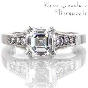 This elegant design features a 1.73 carat asscher cut center diamond in a double prong setting. The tapered band has channel set round diamonds on either side of the center stone and micro pavé on the prongs. There are stunning handmade filigree curls visible from the side profile of this ring.
