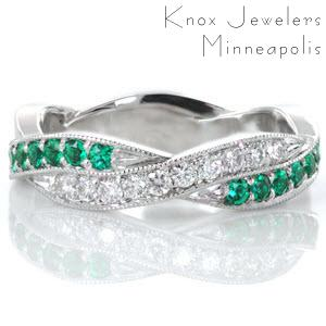 This hypnotic design features a woven pattern where luscious green emeralds intertwine with vibrant white diamonds. All the beautiful gemstones are securely set with shared, bead-set prongs and fashioned in a platinum band. Each segment is edged with a beaded milgrain texture that adds a refined finish to the piece.