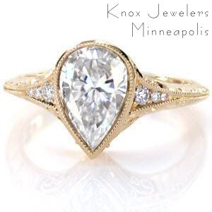 Antique engagement ring in Fargo with pear shape center stone, filigree and hand engraving.