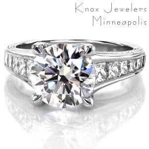 Malay features a 3.25 carat round center stone displayed in a crisscross trellis style four prong design with micro pavé diamond detail along the side. Filigree curls decorate the windows. Graduating princess cut diamonds gleam along the top of the ring, accented in a milgrain edge.