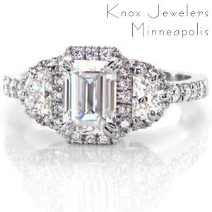 This halo engagement ring features a 1 carat emerald cut and two half moon shaped diamonds. The center stone is prong set with a double prong on each corner. Around these three stones is a halo of small micro pave set diamonds. Both sides of this design feature hand wrought filigree in three pockets.