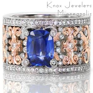 This stunning piece is crowned with a 1.60 carat cushion cut blue sapphire. The prongs holding the center stone each have a bezel set diamond on top. This mesmerizing two-tone wide band is made in 14k white and rose gold with a euro shank for a signature look. The details of the ring are accented with micro pavé