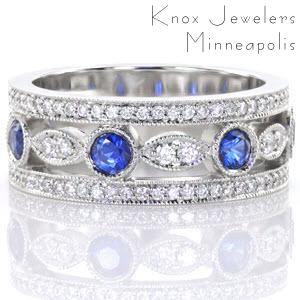 The outside rows of the Sappire Dolce are adorned with micro pavé diamonds and milgrain detail. Alternating marquise shaped patterns and circular outlines detail the center of the design. Vivid blue sapphires fill the circular arrangement and two round brilliant diamonds accent the marquise shaped silhouettes.