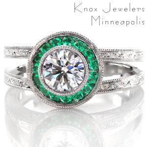 This magnificent design is exquisitely hand crafted with a platinum, split shank band adorned with mesmerizing hand engraving. The center is a bezel set 0.75 carat round brilliant cut diamond surrounded by a micro pavé emerald halo. The basket of the halo has filigree and bezel set surprise diamonds.