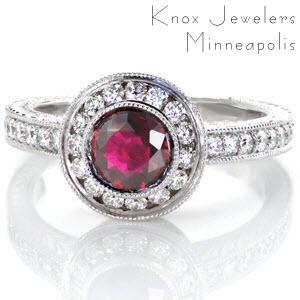 The Ruby Monarch is an enthralling design with a luscious 1.00 carat round ruby center. The center stone is bezel set and surrounded by a halo. Both the halo and band are adorned with micro pavé, with hand engraving on the band and filigree and a bezel set surprise diamond on the basket of the halo.