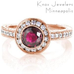 Rose gold and ruby engagement ring in Austin. This perfect combination of the warm rose gold hues, and the red sapphire center stone are exquisitely crafted with a diamond band and diamond halo. This antique engagement ring style also feature hand engraving, hand formed filigree curls, and small bezel set surprise diamonds.