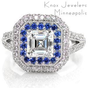 Design 2632 is a regal tribute to the Art Deco style. Taking center attention, a sparkling 1.00 carat asscher cut diamond surrounded by rich blue round cut sapphires. Reaching towards a halo with beveled corners is a split shank band and bezel set surprise diamonds, all set in 14k white gold.