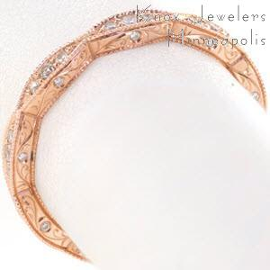 Rose gold wedding ring with marquise-shaped outline from top view and scroll hand engraving from the sides.