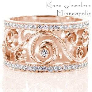 Rose gold wedding band features vintage style filigree curls flanked by micro pave diamonds. A few bezel set diamonds are scattered throughout this unique, flowing design for extra sparkle!