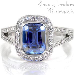 The royal blue of the 2.00 carat cushion cut sapphire is a signature statement of regal expression. Round diamonds outline the sapphire to embellish the beautiful blue of the center stone. The split shank cathedral is lined with bead-set diamonds and accented with two bezel set stones for a majestic finish.