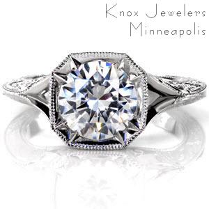 A 2.00 carat round brilliant diamond is proudly displayed in a vintage inspired octagonal bezel with eight delicate pointed prongs. The bezel has a micro pavé diamond apron and filigree detail under the center stone. A knife-edge split shank band is elaborately decorated in hand engraving.
