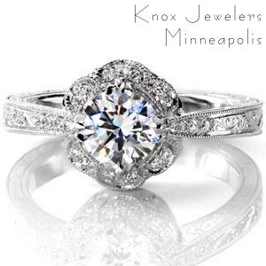This lovely petal design features micro pavé diamonds set within the pattern. The 0.70 carat round center is held by vintage inspired claw prongs. The reverse taper shank delicately adjoins the crown. The piece is embellished with diamonds, hand engraving, milgrain edging and filigree detail.