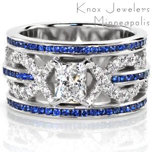 The blue sapphires add a breathtaking pop of color to this signature wide band. The stunning 0.50 carat radiant cut diamond is securely fashioned in 4-prong setting in the center of the design. Micro pavé are seamlessly interwoven along the middle row of sapphires drawing the eye to the brilliant radiant.
