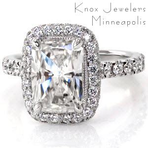 This design is nothing short of regal with the 2.25 carat radiant cut center diamond. The luminous platinum band is carefully detailed with hand cut micro pavé that resembles a U from the side. These U-cuts adorn not only the top of the halo and band, but also the sides, and underside of the halo.