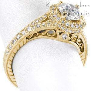 Antique engagement ring with diamond halo, round center stone and filigree in Raleigh.
