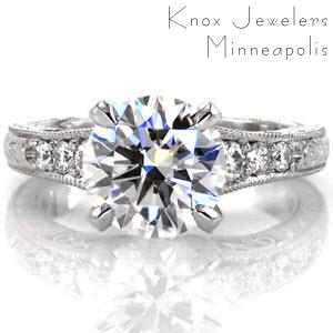 The Meghan Renee features breathtaking antique detail showcasing the 2.00 carat round brilliant cut center diamond. The elegantly beveled claw prongs are decorated in    micro pavé diamond detail for a unique look. The band is embellished with    micro pavé diamonds, hand engraving, filigree curls, and milgrain.