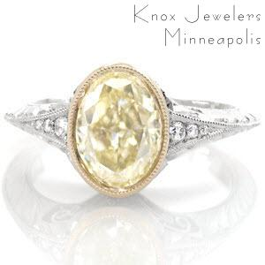 This vintage inspired design puts all attention on the luscious 2.00 carat oval cut fancy yellow diamond center stone. The center is set in an 18k yellow gold bezel to compliment the color of the diamond. The band is fashioned in platinum with a knife edge. The hand formed filigree curls and engraving are mesmerizing.