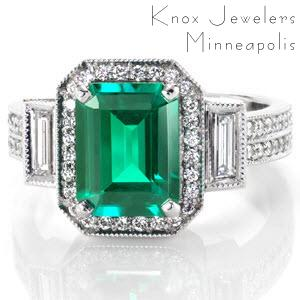 This stunning emerald engagement ring is shown with an emerald cut emerald gemstone center. The band is set with a double row of diamonds leading to baguette side bars which frame the halo.