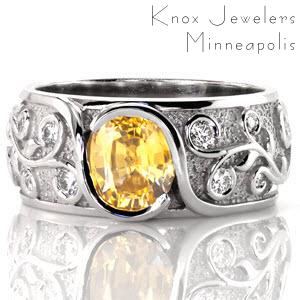 The edges of this interwoven design wrap up and around a bright yellow sapphire, cradling the cushion center in a bezel fashion. Relief engraving of the vines artistically spiral around the shape of a round brilliant diamond. The stipple background adds texture and contrasts the raised high polish engraving.