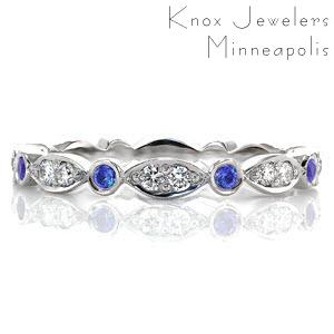 Design 2823 is an eternity band crafted in 14k white gold. Alternating stations of round cut bezel set blue sapphires are accented by a marquise shape pattern with two bead set round brilliant diamonds. The high polish finish accents the vibrancy of the natural blue sapphires and white diamonds.