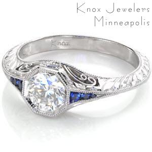 Filigree engagement ring in Madison with blue sapphires, hand engraving and round brilliant center stone.