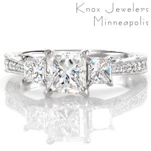 This stunning princess cut three stone setting is elegantly accented with a row of round brilliant diamonds along the length of the band. Intricate antique inspired details of milgrain, filigree and hand engraving embellish the side face of this design. Five petals are embellished with diamonds for a radiant appeal.